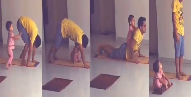 a cute baby do yoga with her father during yoga day in india